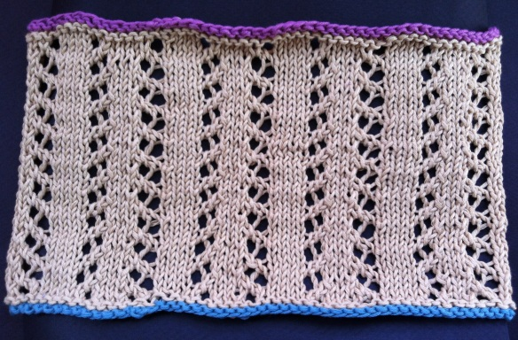 Swatch cowl of Gull Wings reversed panels separated by stockinette sts.
